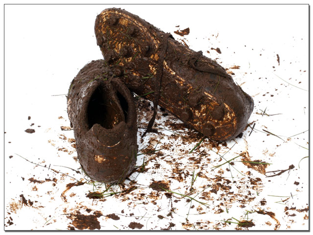 a pair of muddy soccer shoes